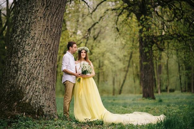 Młodzi nowożeńcy szczęśliwi przytulanie w wiosennym parku