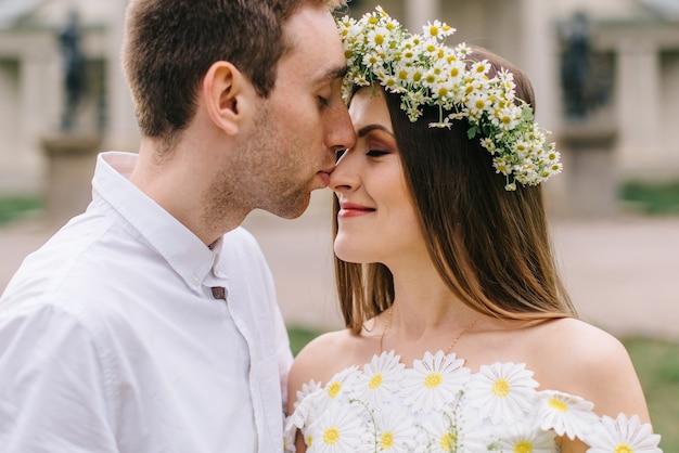 Młodzi nowożeńcy szczęśliwy przytulanie w wiosennym parku, zbliżenie
