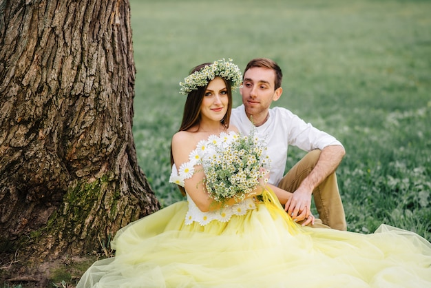 Młodzi nowożeńcy szczęśliwy siedzi na trawie w pobliżu drzewa w parku