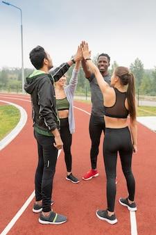 Młodzi, odnoszący sukcesy, międzykulturowi przyjaciele w strojach sportowych dotykający dłońmi stojąc w kręgu na stadionie