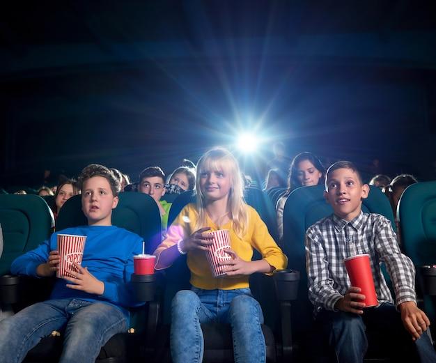 Młodzi oglądają film i jedzą przekąski w kinie.