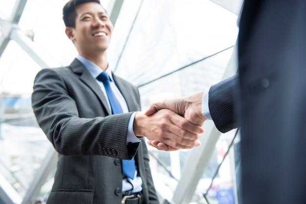 Młodzi partnerzy biznesowi robi uścisk dłoni