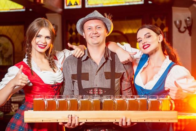 Młodzi piękni kelnerzy w strojach ludowych na imprezie oktoberfest z ogromną tacą po piwie.