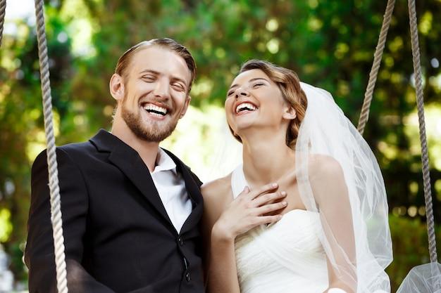 Młodzi piękni nowożeńcy uśmiecha się, śmia się, siedzący na huśtawce w parku.