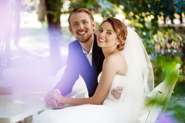 Młodzi piękni nowożeńcy uśmiechając się, obejmując, siedząc w kawiarni na świeżym powietrzu.