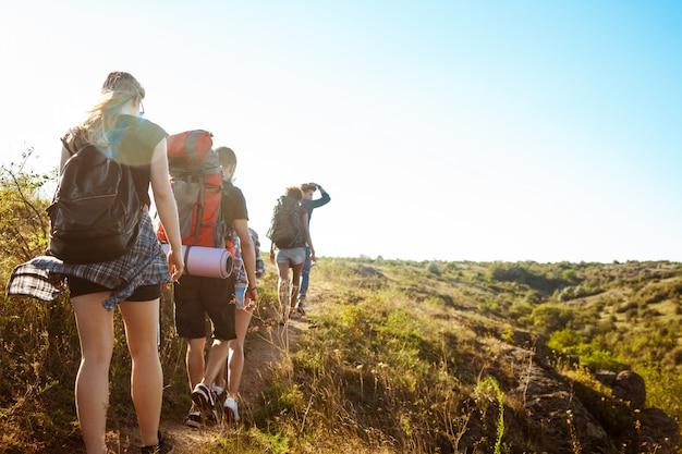 Młodzi piękni przyjaciele podróżują z plecakami w kanionie