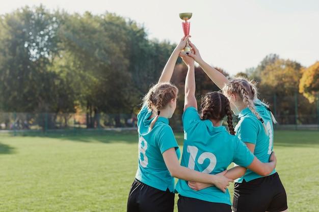 Młodzi piłkarze podnoszący trofeum