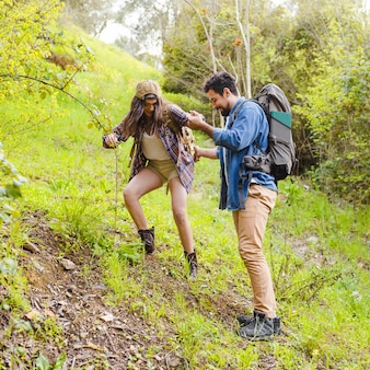 Młodzi podróżni wspinają się wzgórze