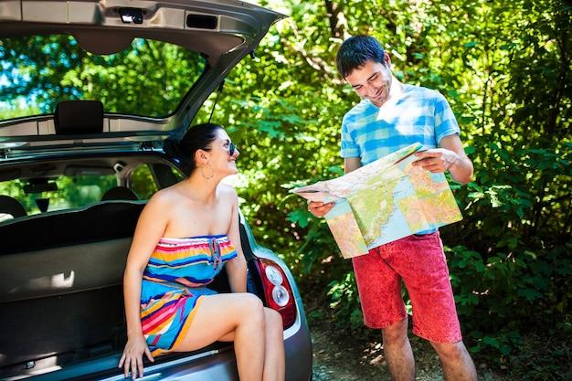 Młodzi podróżnicy patrząc na mapę, siedząc w bagażniku samochodu