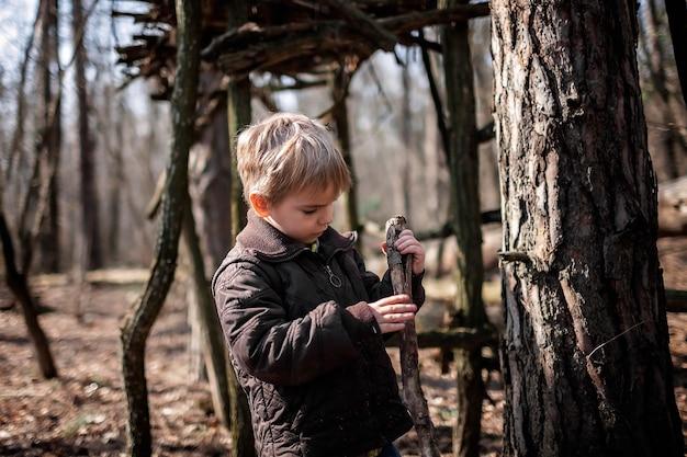Młodzi poszukiwacze przygód budujący drewniane siedlisko w dzikim lesie podczas towarzyskich spacerów na odległość