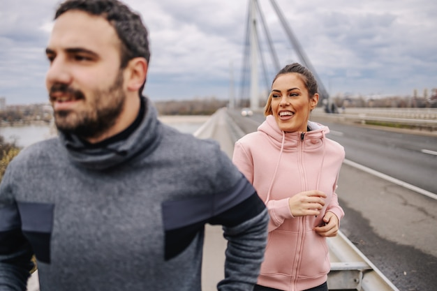 Młodzi pozytywnie uśmiechnięci heteroseksualni przyjaciele w odzieży sportowej biegający po moście w pochmurną pogodę.