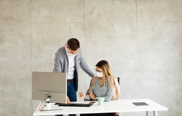 Młodzi pracownicy biznesowi noszą maski, aby chronić i dbać o swoje zdrowie podczas pracy przy komputerze