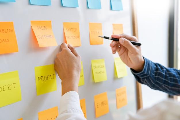 Młodzi pracownicy biznesowi wysyłający naklejki z karteczkami przypominają kreatywną burzę mózgów na pokładzie kolegi w nowoczesnej przestrzeni coworkingowej.