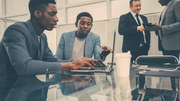 Młodzi pracownicy korzystający z laptopa w biurze