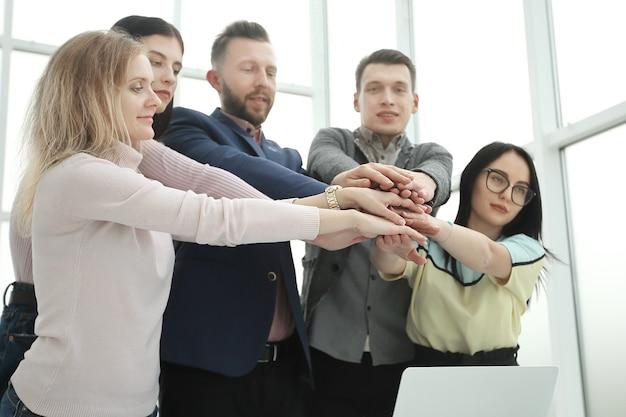 Młodzi pracownicy łączą ręce nad biurkiem