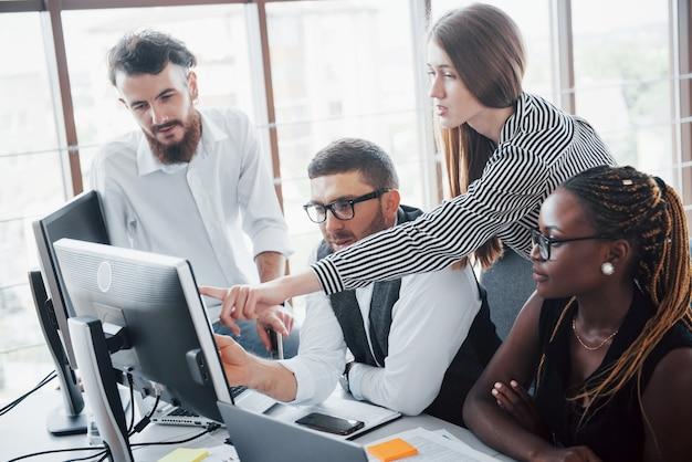 Młodzi pracownicy siedzący w biurze przy stole i korzystający z laptopa