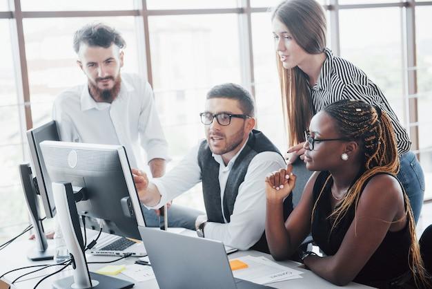 Młodzi pracownicy siedzi w biurze przy stole i używa laptopu, pracy zespołowej burzy mózgów spotkania pojęcie.