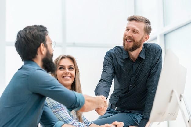Młodzi profesjonaliści podają sobie ręce w miejscu pracy. pojęcie pracy zespołowej