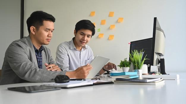 Młodzi programiści pracujący na komputerze i tablecie w nowoczesnym biurze pracy.