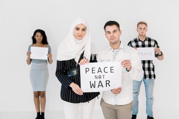 Młodzi protestujący, muzułmanka i kaukaski mężczyzna, skandujący, by ocalić pokój, trzymający plakat z hasłem bez wojny