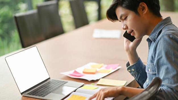 Młodzi przedsiębiorcy dzwonią do pracy i korzystają z laptopa.