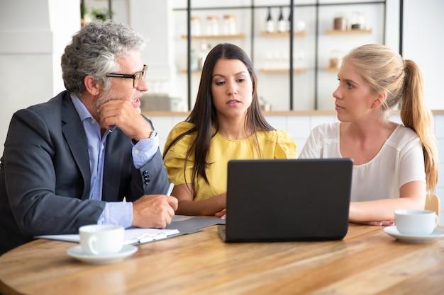Młodzi przedsiębiorcy i dojrzały inwestor oglądają prezentację i omawiają projekt