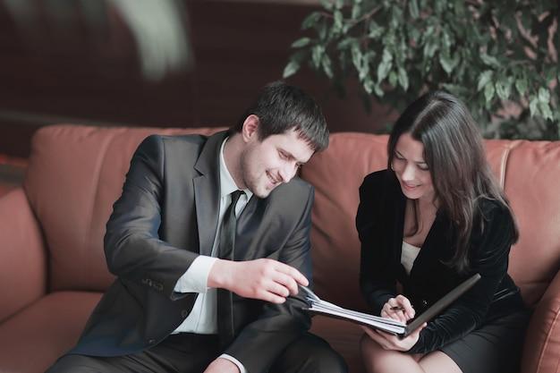 Młodzi przedsiębiorcy omawiają dokument biznesowy, siedząc na kanapie w centrum biznesowym. zdjęcie z miejsca na kopię