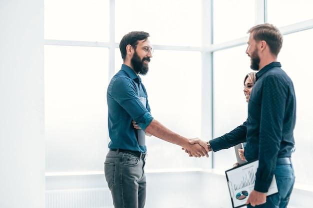 Młodzi przedsiębiorcy ściskają sobie ręce. koncepcja współpracy