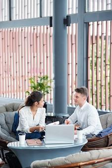 Młodzi przedsiębiorcy spotykają się w restauracji, aby omówić sposoby współpracy, raporty i kontrakty