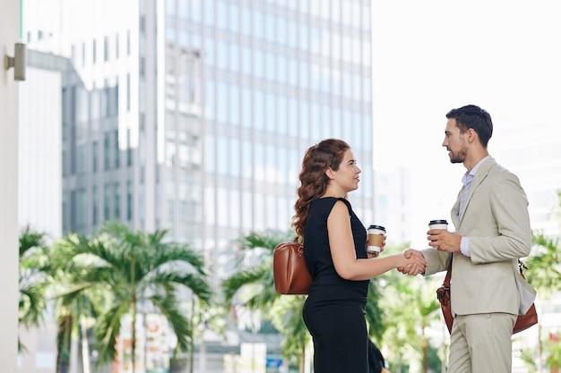 Młodzi przedsiębiorcy stoją na ulicy z kawą na wynos i uściskiem dłoni