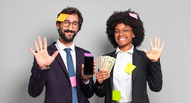 Młodzi przedsiębiorcy uśmiechnięci i patrząc przyjaźnie, pokazując numer pięć lub piąty ręką do przodu, odliczając w dół. humorystyczna koncepcja biznesowa