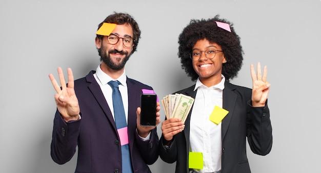 Młodzi przedsiębiorcy uśmiechnięci i przyjaźnie wyglądający, pokazujący numer trzy lub trzeci z ręką do przodu, odliczający. humorystyczny pomysł na biznes
