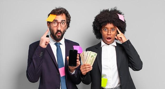 Młodzi przedsiębiorcy wyglądający na zaskoczonych, z otwartymi ustami, zszokowani, realizujący nową myśl, pomysł lub koncepcję. humorystyczna koncepcja biznesowa