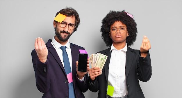 Młodzi przedsiębiorcy wykonujący gest kaprysu lub pieniędzy, nakazujący spłatę długów!. humorystyczna koncepcja biznesowa
