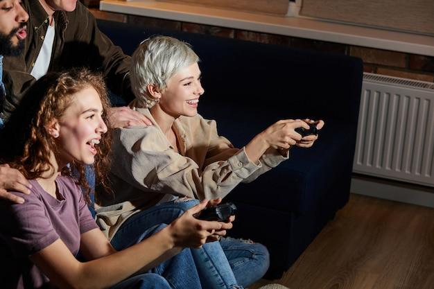 Młodzi przyjaciele bawią się grając w konsolę w domu, w pomieszczeniu, wieczorem lub w nocy. przyjaźń, wypoczynek, odpoczynek, koncepcja przyjęcia w domu