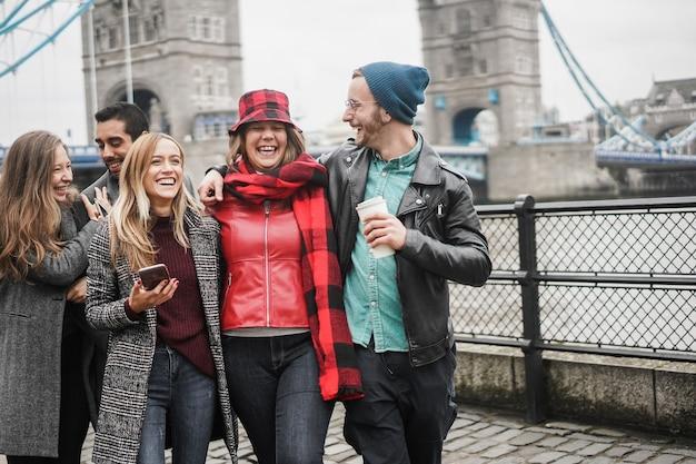 Młodzi przyjaciele bawią się na świeżym powietrzu w mieście obok tower bridge w londynie – skup się na twarzach dziewczynki w centrum