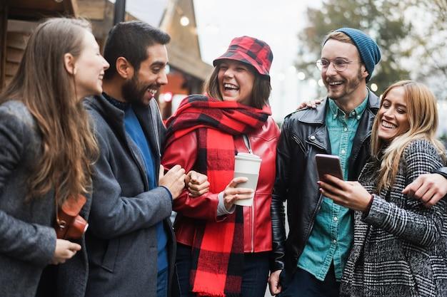 Młodzi przyjaciele bawią się na świeżym powietrzu w mieście w zimowy dzień - skup się na twarzy kobiety w centrum
