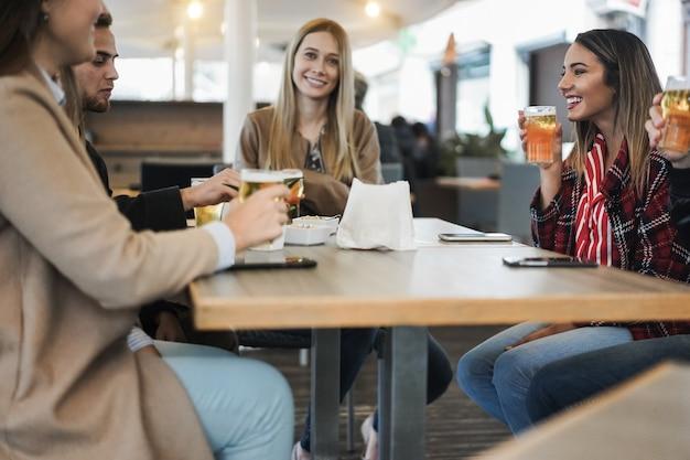 Młodzi przyjaciele bawią się razem pijąc piwo w restauracji barowej - skoncentruj się na prawej twarzy kobiety