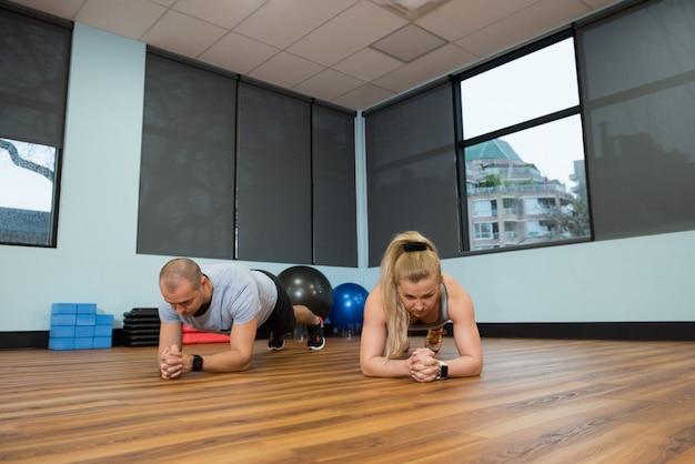 Młodzi przyjaciele ćwiczy na drewnianej podłoga
