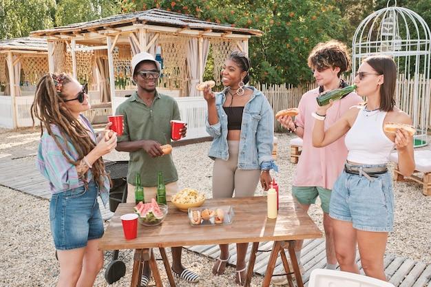 Młodzi przyjaciele jedzący hot dogi i napoje na świeżym powietrzu