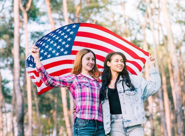 Młodzi przyjaciele kobiece przytulanie i macha amerykańską flagę