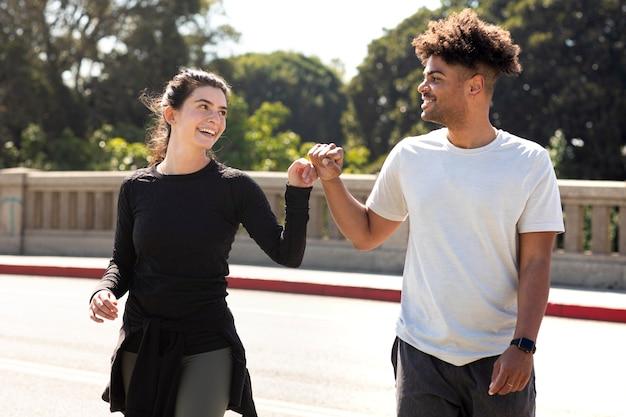 Młodzi przyjaciele na joggingu robią uderzenie pięścią