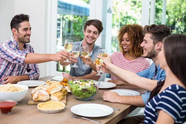 Młodzi przyjaciele opiekania wino podczas posiłku przy stole