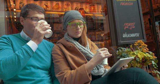 Młodzi przyjaciele piją coffeetogo na świeżym powietrzu
