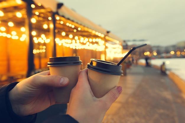Młodzi przyjaciele piją kawę w papierze zabierają kubek