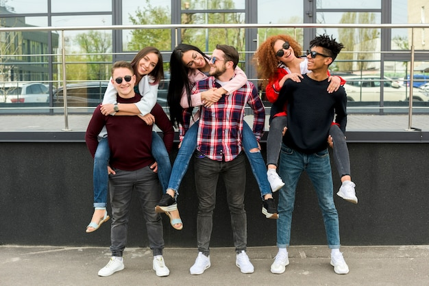 Młodzi przyjaciele płci męskiej niosący piggyback swoim koleżankom