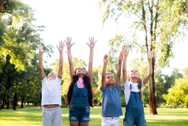 Młodzi przyjaciele, podnosząc ręce w powietrzu