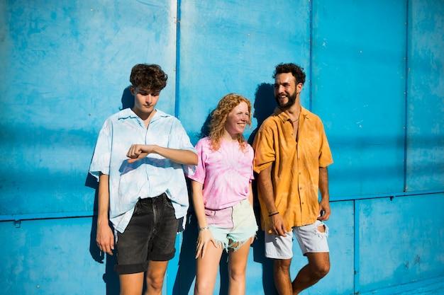 Młodzi przyjaciele pozuje z błękitnym tłem