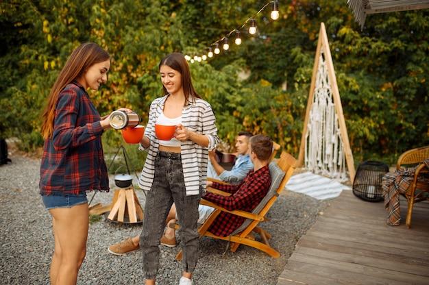 Młodzi przyjaciele relaksują się na pikniku na kempingu w lesie. młodzież przeżywa letnią przygodę na kamperze, samochodzie kempingowym dwie pary odpoczywa, podróżuje z przyczepą
