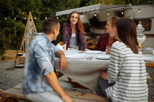 Młodzi przyjaciele relaksują się na pikniku na kempingu w lesie